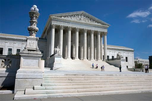 People walk on the steps of the U.S. Supreme Court in Washington on Saturday April 26, 2014.