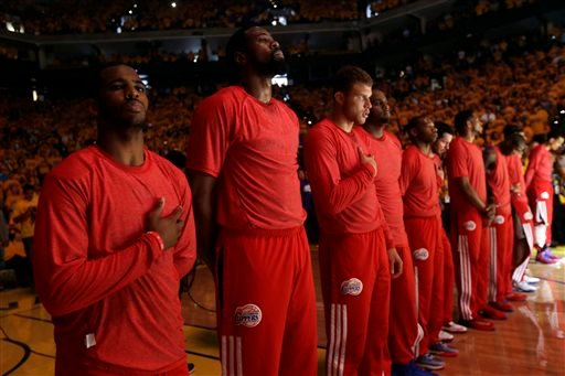 Members of the Los Angeles Clippers listen to the national anthem before Game 4 of an opening-round NBA basketball playoff series against the Golden State Warriors on Sunday, April 27, 2014, in Oakland, Calif.