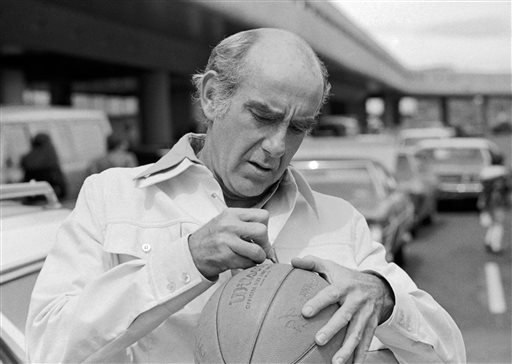 In this Friday, May 28, 1977, file photo, Portland Trail Blazers head coach Jack Ramsay autographs a basketball as the team arrived in Portland, Ore.