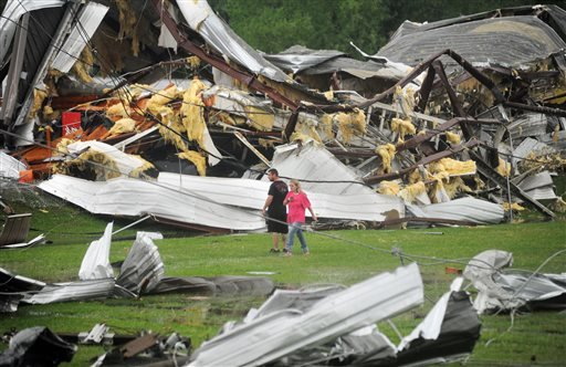 A man and woman examine the twisted wreckage of Glass Masters on U.S. 49 Frontage Road in Richland, Miss., shortly after it was destroyed by a tornado late Monday afternoon, April 28, 2014.