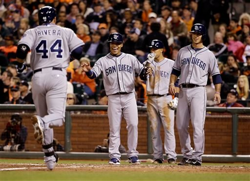 San Diego Padres' Rene Rivera (44) is greeted at the plate by teammates Alexi Amarista, center left, and Tommy Medica, right, after Rivera's three-run home run against the San Francisco Giants during the fifth inning of a baseball game April 28, 2014.