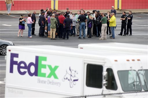 A police officer, center, talks with FedEx employees as they wait to meet their family at a nearby business after they were evacuated from the Airport Road FedEx facility after an early morning shooting Tuesday April 29, 2014, in Kennesaw, Ga. (AP)