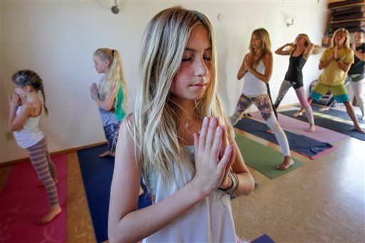 Yoga teacher Jaysea DeVoe, 12, leads a yoga class at Bergamot Spa & Boutique in Encinitas, Calif., on Tuesday, April 29, 2014.