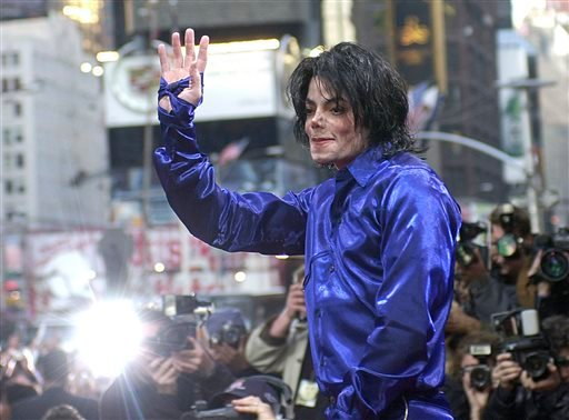 """Nov. 7, 2001 file photo, Michael Jackson waves to crowds gathered to see him at his first ever in-store appearance to celebrate his new album """"Invincible"""" in New York's Times Square."""