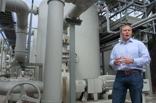 In this April 25, 2014 photo, Joshua Haggmark, interim resources manager for Santa Barbara, Calif., stands next to a desalination plant, which removes salt from ocean water, in Santa Barbara, Calif.