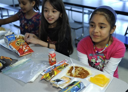 In this Tuesday, April 29, 2014 photo, Brianna Delcid-Gomez, 7, right, Ruth Gebregiorgis, 8, far left, and Amina Sharif, 7, center, eat lunch at the Patrick Henry Elementary School in Alexandria, Va.