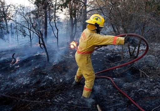 An Edmond firefighter moves a hose while battling a fire at 1600 E Forrest Hills during Oklahoma wildfires in south Logan County, Sunday, May 4, 2014.