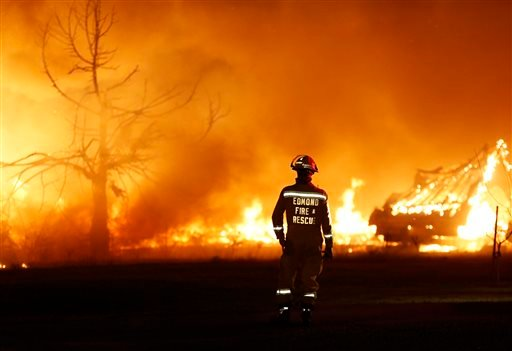 An Edmond firefighter looks at a fire raging in a mobile home park near Prairie Grove Rd. and Douglas during Oklahoma wildfires in Logan County, Sunday, May 4, 2014.