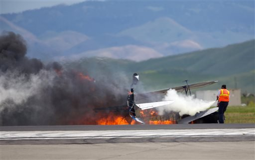 A worker fights a fire after a vintage biplane crashed upside-down on a runway at an air show at Travis Air Force Base in Fairfield, Calif., Sunday, May 4, 2014.
