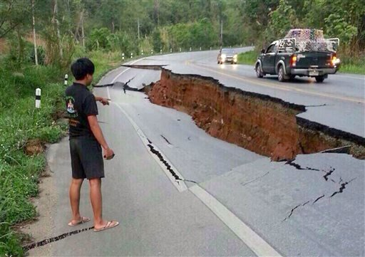 A man points a big crack on a damaged road following a strong earthquake in Phan district of Chiang Rai province, northern Thailand, Monday, May 5, 2014.