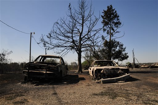 The charred remains of two cars are left on Monday, May 5, 2014, in Guthrie, Okla., the day after a wildfire tore through the area.