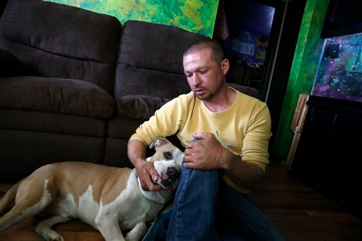 Wayne Winkler, who suffered burns to 12 percent of his body when butane fumes ignited while he was making hash oil at home, pets his dog Bailey, in his living room, in Denver, May 1, 2014.