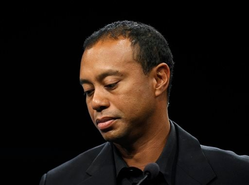 In this March 24, 2014 file photo, Tiger Woods looks down during a news conference at the Newseum in Washington.