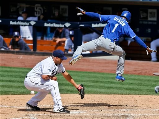 Kansas City Royals' Jarrod Dyson sails through the air while scoring over San Diego Padres pitcher Hector Ambriz after a passed ball during the eighth inning of a baseball game.