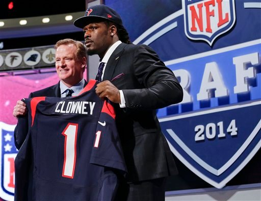 South Carolina defensive end Jadeveon Clowney holds up the jersey for the Houston Texans first pick of the first round of the 2014 NFL Draft with NFL commissioner Roger Goddell, Thursday, May 8, 2014, in New York.