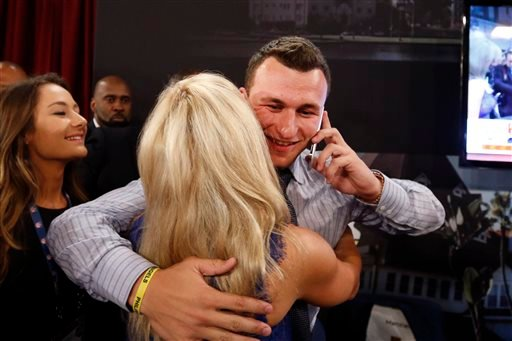 Johnny Manziel, from Texas A&M, is congratulated after being selected 22nd overall in the first round of the NFL football draft by the Cleveland Browns, Thursday, May 8, 2014, at Radio City Music Hall in New York.