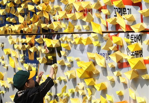 A boy attaches a paper ship on the police bus near the presidential Blue House in Seoul, South Korea, Friday, May 9, 2014.