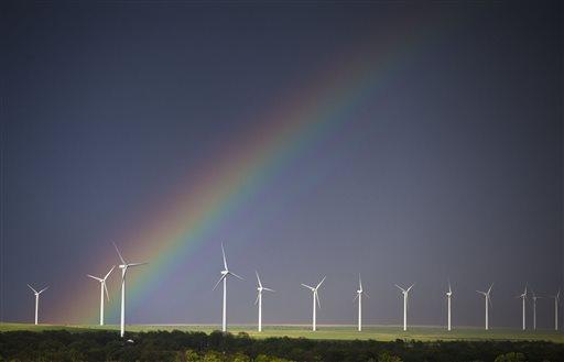 A rainbow forms over a wind-energy farm near Latham, Kan., on Thursday, May 8, 2014.