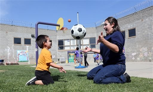 In this photo taken May 3, 2014, inmate Erica Carmona, 21, tosses a soccer ball back and forth with her son, Dominic, 3, during his visit to the Folsom Women's Facility in Folsom Calif.