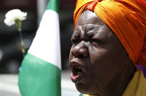 Activist Dr. Delois Blakely chants while holding a flower and the flag of Nigeria during a rally in front of the Nigerian consulate, Saturday, May 10, 2014, in New York.