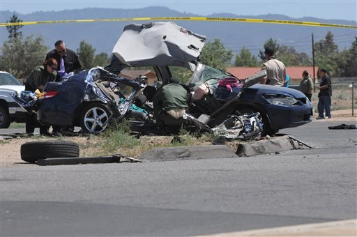 Authorities work on the scene of a fatal traffic accident in Hesperia, Calif, Sunday, May 11, 2014.