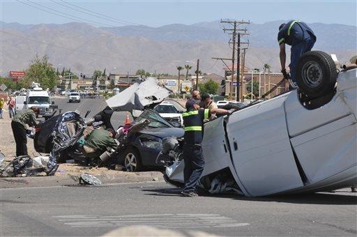A spokeswoman with the San Bernardino County Sheriff's Department says that four people are confirmed dead after a van smashed into a car that was sitting at a stop sign. (AP Photo/The Victor Valley Daily Press, David Pardo)