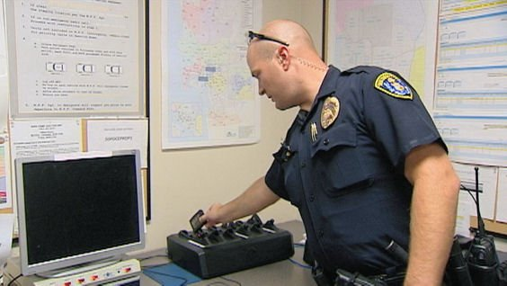 Officer David Peplowski places body cam in docking station for video upload to server