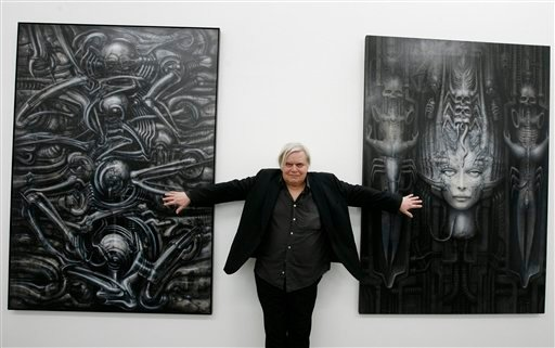 In this June 29, 2007 file picture Swiss artist H.R. Giger poses with two of his works at the art museum in Chur, Switzerland.