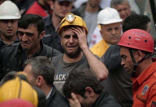 A miner cries as rescue workers carry the dead body of a miner from the mine in Soma, western Turkey, Wednesday, May 14, 2014.