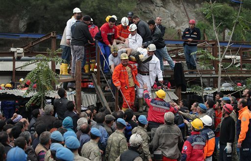 Rescue workers carry a rescued miner from the mine in Soma, western Turkey, early Wednesday, May 14, 2014.