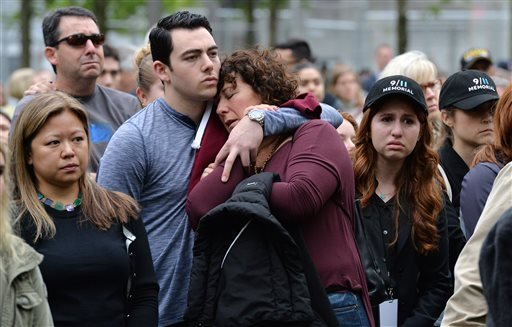Two people embrace while gathered on the plaza of the National September 11 Memorial to watch the telecast of the dedication ceremony at the National September 11 Memorial Museum in New York on Thursday, May 15, 2014.