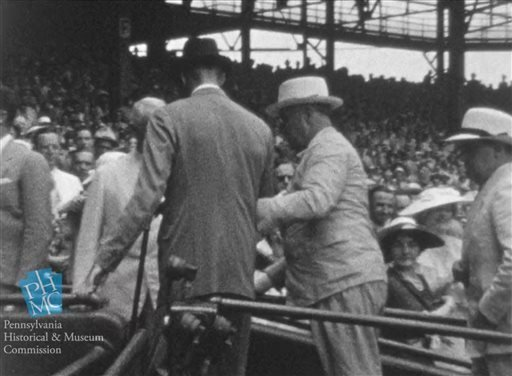 In this image taken from film shot by former Major League Baseball player Jimmie DeShong and acquired by the Pennsylvania Historical & Museum Commission, President Franklin D. Roosevelt, center right, walks to his seat with the aid of an assistant.