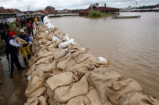 People build a dam made up of sandbags by the bank of the Sava river in Sremska Mitrovica, 90 kilometers west of Belgrade, Serbia, Saturday, May 17, 2014.