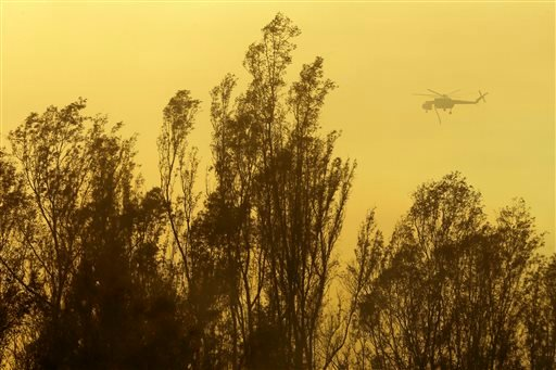 A helicopter transporting water flies over trees during a wildfire Thursday, May 15, 2014, in Escondido, Calif.
