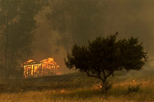 Fire engulfs a structure during a wildfire Thursday, May 15, 2014, in Escondido, Calif. One of the nine fires burning in San Diego County suddenly flared Thursday afternoon and burned close to homes, trigging thousands of new evacuation orders.
