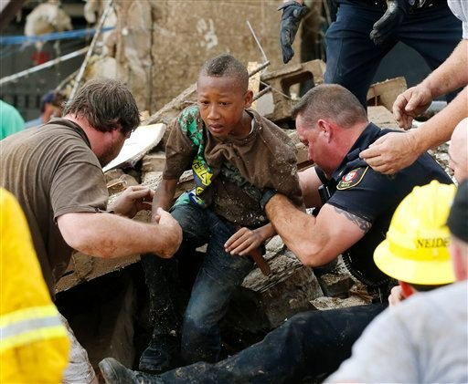 In this May 20, 2013 file photo, Cam'ron Richardson, center, is carried out of the rubble of Plaza Towers Elementary school after a massive tornado hit in Moore, Okla.