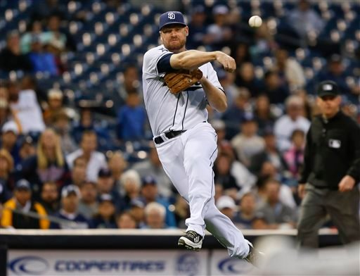 San Diego Padres third baseman Chase Headley makes a running throw after fielding a slow roller by Minnesota Twins' Trevor Plouffe during the sixth inning of a baseball game May 21, 2014, in San Diego. Plouffe was safe at first. (AP Photo/Lenny Ignelzi)