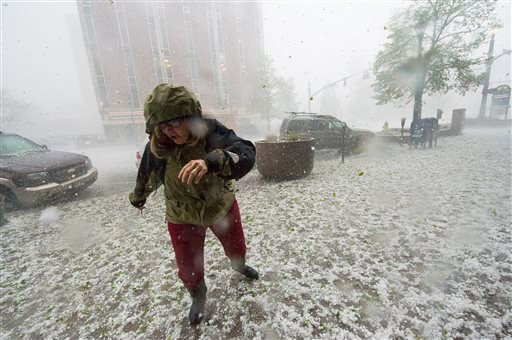 A pedestrian runs for safety as a hail storm hits downtown Colorado Springs, Colo., Wednesday, May 21, 2014.