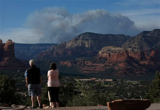 Tourists watch the Slide Fire from a scenic overlook as it burns up Oak Creek Canyon nearby on Thursday, May 22, 2014, in Sedona, Ariz. The fire has burned approximately 4,800 acres. (AP Photo/Ross D. Franklin)