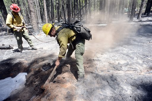 U.S. Forest Service firefighting crews work hotspots Thursday May 22, 2014 near Sedona, Ariz .The human-caused Slide Fire started Tuesday. (AP Photo/ Vyto Starinskas)