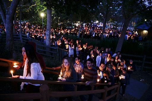 People gather at a park for a candlelight vigil to honor the victims of Friday night's mass shooting on Saturday, May 24, 2014, in Isla Vista, Calif. (AP Photo/Jae C. Hong)