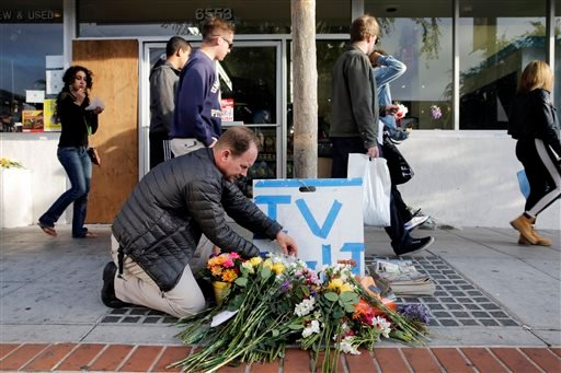 Stephen Nichols arranges flowers left in front of IV Deli Mart, where part of Friday night's mass shooting took place by a drive-by shooter, on Saturday, May 24, 2014, in Isla Vista, Calif.  (AP Photo/Jae C. Hong)