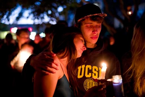 Two students comfort each other during a candlelight vigil held to honor the victims of Friday night's mass shooting on Saturday, May 24, 2014, in Isla Vista, Calif.