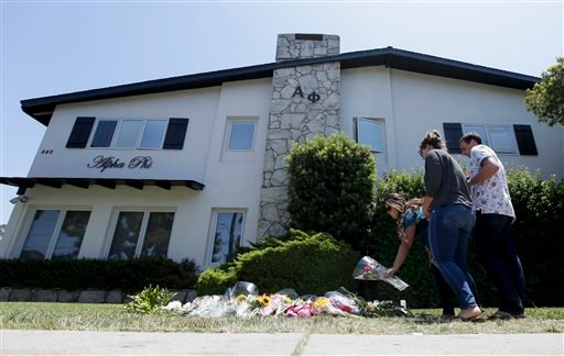 Patty Ritter, from left, 21, Rachel Keever, 22, and Craig Schaffer, 20, put flowers on a makeshift memorial at the Alpha Phi sorority house, Sunday, May 25, 2014, where two women were killed in Friday night's mass shooting in the Isla Vista area. (AP)