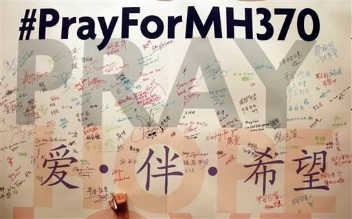 In this April 6, 2014 file photo, a man writes messages for passengers aboard the missing Malaysia Airlines Flight MH370 before a mass prayer for them, in Kuala Lumpur, Malaysia.
