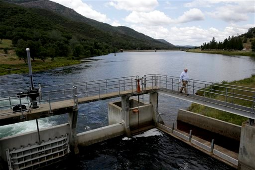 In this May 6, 2014 photo, Steven Ritchie, an assistant general manager of San Francisco Public Utilities Commission, walks on a bridge over Moccasin reservoir at the Moccasin Powerhouse in Moccasin, Calif.