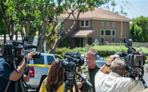 Lt. Jeff Hallock of the Orange County Sheriff's Department speaks with the media about the discovery of four bodies in the home behind him in Mission ViejoTuesday morning, May 27, 2014. (AP)