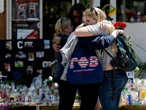Mourners hug in front of the IV Deli Mart, where part of Friday night's mass shooting took place, on Tuesday, May 27, 2014 in the Isla Vista area near Goleta, Calif. (AP)