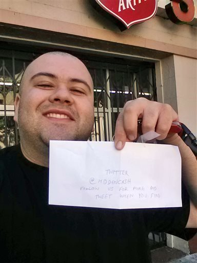 This image provided by Sergio Loza shows Loza holding up an envelope that had cash hidden in it in San Francisco May 25. Loza followed the clues from a Twitter user using the handle @HiddenCash to find the money. (AP Photo/Sergio Loza)