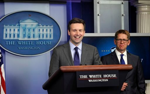 White House press secretary Jay Carney listens at right as Principal Deputy press secretary Josh Earnest takes to the stage for part of the daily briefing at the White House in Washington, Friday, May 30, 2014.